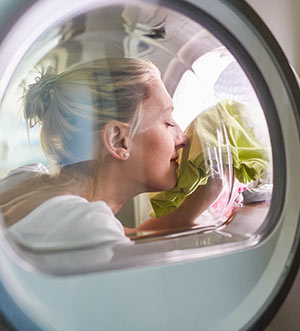 woman testing smell of clothes in dryer