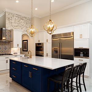 white kitchen with navy island and brass hardware